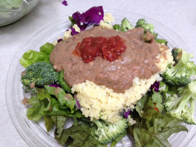 Mashed beans, salsa and millet served on top of salad.